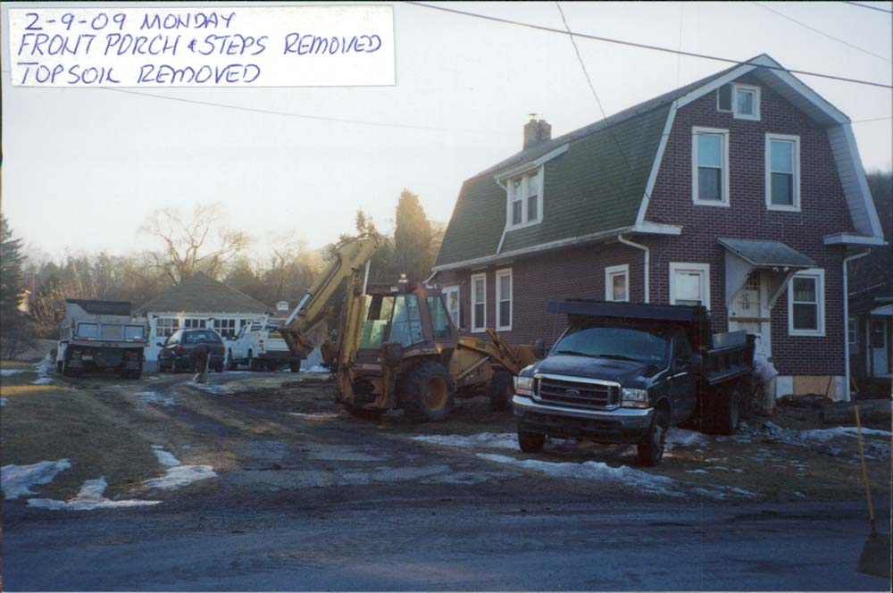 brick home with construction vehicle parked on the side